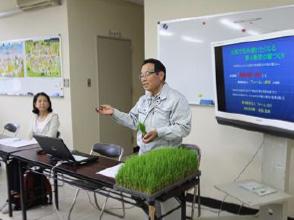 苗を手に稲の成長を説明す吉弘組合長